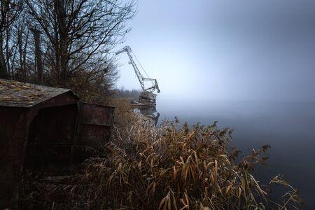 Rusty old industrial dock cranes at swampland