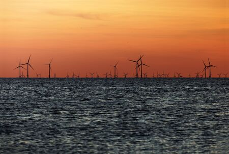 Windfarm on the sea at sunset closeup footage