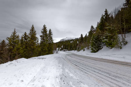 Snowy mountain road streching through the hills under cloudy sky