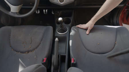 Man cleaning dirty car interior with vacuum cleaner closeup