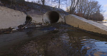 Large sewage tunnel with filth flowing out angle shot