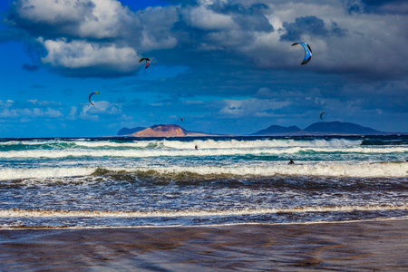 wales: Surfers and kiters in the water on Famara beach, Lanzarote Stock Photo