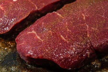 A steak seasoned with pepper is ready to be fried, but only a minute on each side for a juicy result