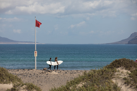 paso de peatones: The red flag weighs in the wind at Surfers Beach Famara on Lanzarote.
