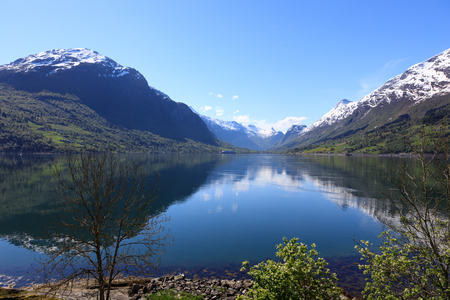 jostedal: A wonderful beautiful spring day in Loen in Sogn with green trees and snowy mountains.