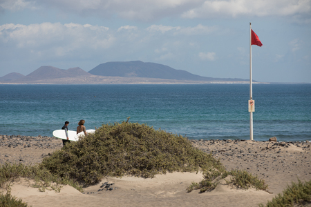 The red flag weighs in the wind at Surfers Beach Famara on Lanzarote.