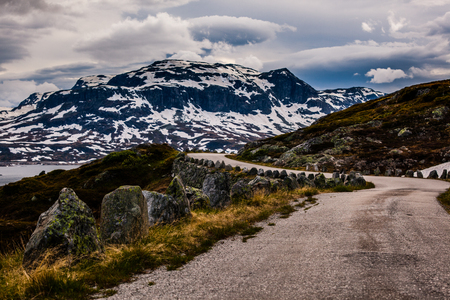 Gravel road on Hardangervidda, Norway, an autumn day with snow on the mountain tops.