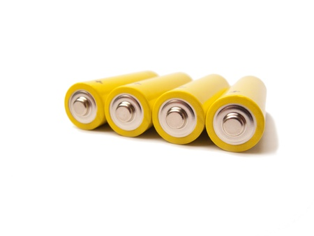 Four yellow batteries with the contacts showing, white background