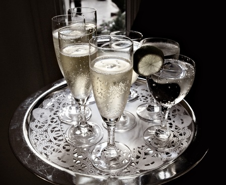 serving tray: A waiter serves sparkling wine and water on a silver tray