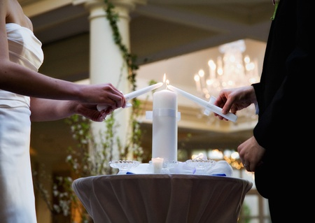 Bride and Groom lighting a white unity candle at their wedding Imagens