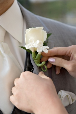 attaching: Woman attaching a white bouttonniere to mans gray suit Stock Photo