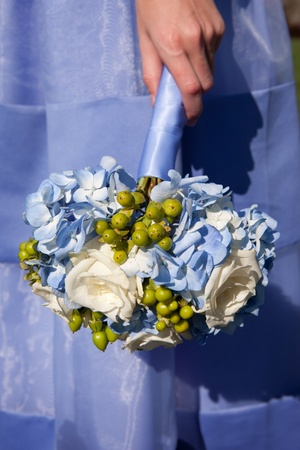 Bridesmaid holding blue flowers in her hand
