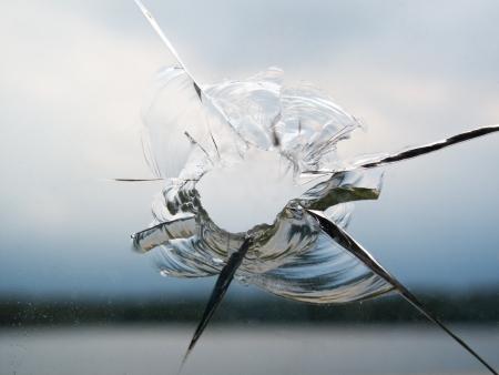 Loch in einem gebrochenen Fenster Standard-Bild