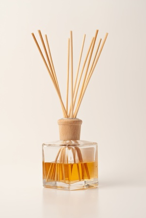 Perfumed incense sticks in an oil jar on clean background