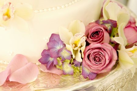 wedding reception decoration: Wedding Cake lined with Tropical Flowers and Roses