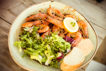 Plate of freshly grilled Gambas with salad, lemon, and bread