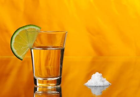 Tequila shot mit ein halbes Stück Kalk auf dem Glas und einen Haufen von Salz von der Seite auf orange Hintergrund (Tiefenschärfe)
