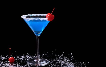 curacao: Blue Curacao drink in a glass with coconut flake rim and a maraschino cherry surrounded by coconut flakes and a maraschino cherry photographed on black (Selective Focus, Focus on the front of the glass and the cherry on the rim) Stock Photo