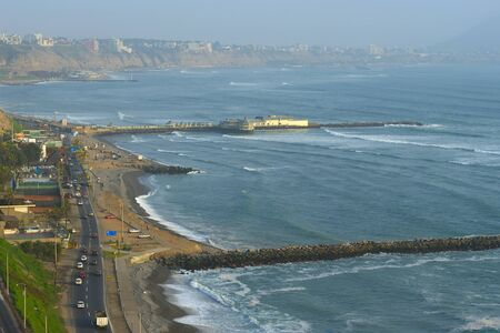 miraflores: The seaside road in Miraflores and a restaurant built on the pier, with a view on the coastline of Southern Lima in the usual misty weather. The surf breaks are used by many tourists and locals to learn surfing.  Stock Photo