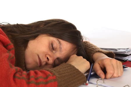 Young Caucasian woman fell asleep while writing and studying. Isolated on white (Selective Focus, Focus on the right eye and the right side of the face) photo