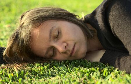 Young Caucasian woman sleeping on grass in a park lit by the evening light (Selective Focus, Focus on the left eye) Stock Photo - 10555413