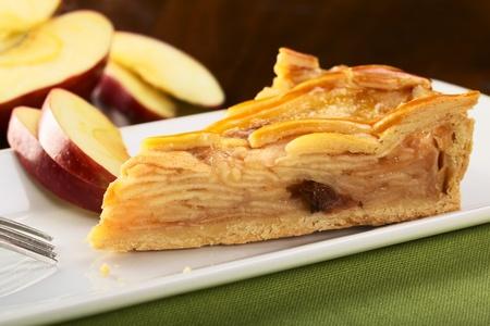 pastel de manzana: Un trozo de pastel de manzana deliciosa con rodajas de manzana en la espalda (enfoque selectivo, centrarse en la parte frontal izquierda)