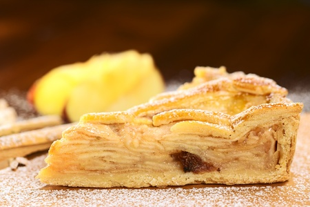 A slice of delicious apple pie with sugar powder (Selective Focus, Focus on the upper edge of the pie) photo