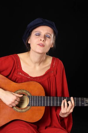 soulful eyes: Young Caucasian woman singing and playing the guitar with eyes closed (Selective Focus, Focus on the face)