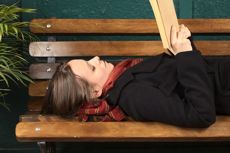 Young Caucasian woman lying on a bench reading a book (Selective Focus, Focus on the right eye) Stock Photo - 10894144