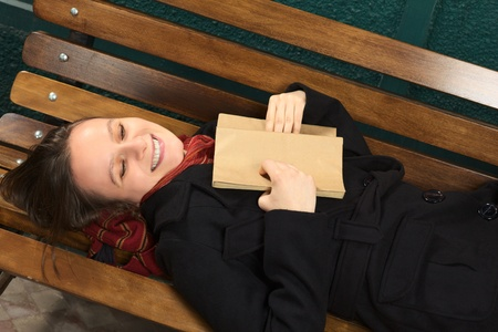 Young happy Caucasian woman lying on a bench reading a book (Selective Focus, Focus on the face) Stock Photo - 10894146