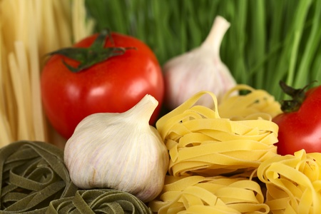 Raw tagliatelle paglia e fieno (straw and hay) with raw garlic bulb and globe tomato (Selective Focus, Focus on the front of the upper yellow tagliatelle pile and parts of the garlic bulb beside) Stock Photo - 10894138