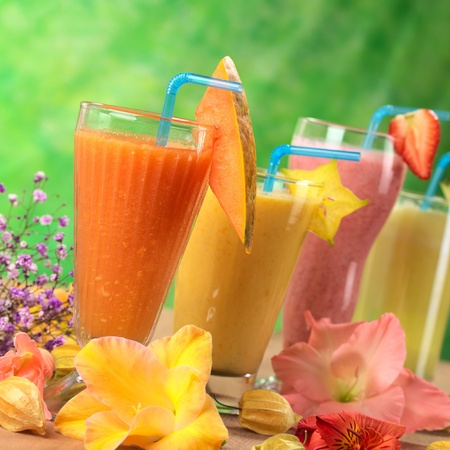 Fresh papaya, mango, strawberry and pineapple fruit juices and milkshakes decorated with flowers (Selective Focus, Focus on the papaya juice and the papaya slice garnish) Stockfoto