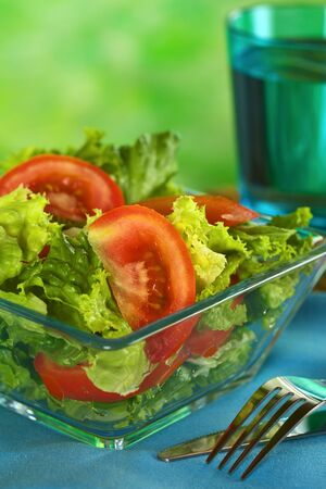 Fresh salad of lettuce and tomato with a glass of water in the back (Selective Focus, Focus on the tomato slice in the front)  Stock Photo - 12028516