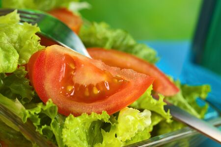Fresh salad of lettuce and tomato (Selective Focus, Focus on the seeds of the tomato slice in the front)  photo