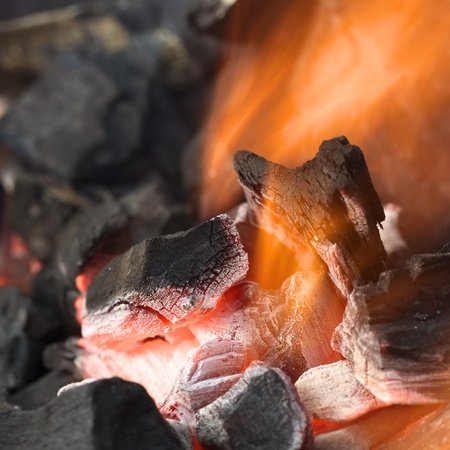 Burning charcoal with orange-colored flame and glow (Selective Focus, Focus on parts of the charcoal pieces around the flame) photo