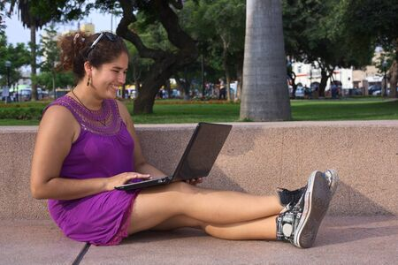 Beautiful smiling young Peruvian woman with laptop computer in a park in Lima, Peru (Selective Focus, Focus on the face of the woman) photo