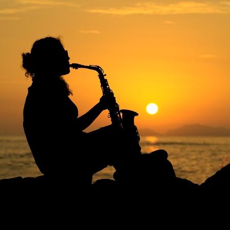 musical instruments: La silueta de una mujer joven m�sico tocando su saxof�n en la costa al atardecer