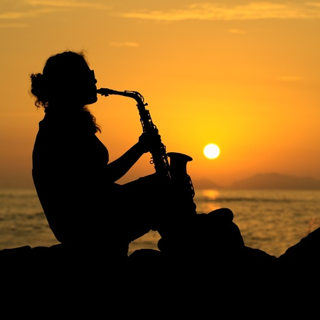 The silhouette of a young female musician playing her saxophone on the coast at sunset photo