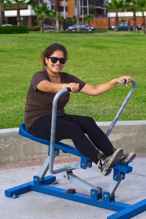 leverage: Young latina doing some exercise in a park on a leverage training equipment  Stock Photo