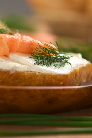 Canape of smoked salmon and cream cheese on wholewheat bun garnished with dill (Selective Focus, Focus on the front of the dill) photo