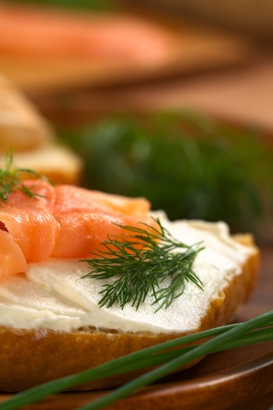 Canape of smoked salmon and cream cheese on wholewheat bun garnished with dill, chives on the side (Selective Focus, Focus on the front of the dill and on the front of the salmon on the left) photo