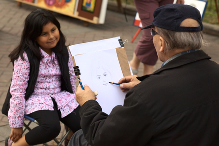 miraflores: LIMA, PERU - SEPTEMBER 25, 2011: Unidentified street artist drawing a picture of an unidentified young Peruvian girl on September 25, 2011 in the district of Miraflores in Lima, Peru (Selective Focus, Focus on the drawing)