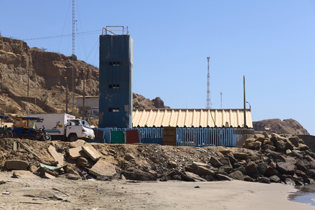 mototaxi: MANCORA, PERU - AUGUST 17, 2013: Entrance to the harbor of Mancora and place where fish get packaged and put on trucks on August 17, 2013 in Mancora, Peru. Mancora is a small town in Northern Peru that lives from fishing and tourism.   Editorial