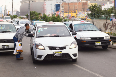 beforehand: LIMA, PERU - JULY 21, 2013  Unidentified man asking a taxi for the fare on Av  Paseo de la Republica in the city center on July 21, 2013 in Lima, Peru  In Lima, taxi fares are agreed upon beforehand, fares are not standardized