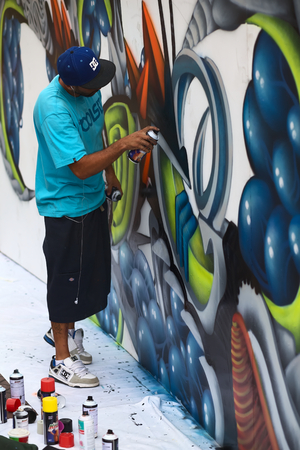 miraflores: LIMA, PERU - MARCH 3, 2012  Unidentified young man spraying a wall on the Latir Latino, the first Latin-American Street Art Festival on March 3, 2012 in Miraflores, Lima, Peru  Many national and international street artists participated on this Festival,