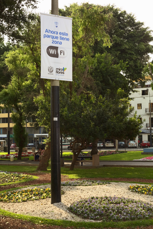 LIMA, PERU - DECEMBER 13, 2011  Wifi-Zone sign with unidentified people in the back in the Kennedy Park in the district of Miraflores on December 13, 2011 in Lima, Peru  Miraflores is one of the most modern districts of Lima, where the municipality invest