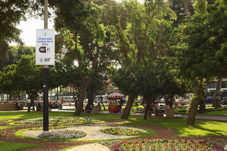 miraflores: LIMA, PERU - DECEMBER 13, 2011  Wifi-Zone sign with unidentified people in the back in the Kennedy Park in the district of Miraflores on December 13, 2011 in Lima, Peru  Miraflores is one of the most modern districts of Lima, where the municipality invest
