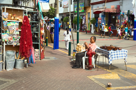 LIMA, PERU - FEBRUARY 13, 2012  Unidentified man selling kitchen utensils and wooden toys at the entrance of the market called Mercado No 1 de Surquillo on February 13, 2012 in Lima, Peru