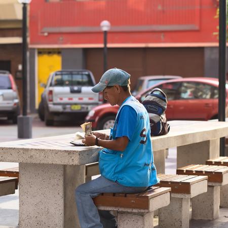 miraflores: LIMA, PERU - MARCH 5, 2012  Unidentified street money exchanger counting dollar bills at an outdoor table in Miraflores on March 5, 2012 in Lima, Peru  Mobile money exchangers on the streets are very common in Lima