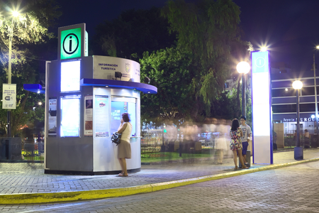 LIMA, PERU - MARCH 5, 2012  Unidentified person at the tourist information at Kennedy Park in the district of Miraflores in the evening on March 5, 2012 in Lima, Peru  Miraflores is the most touristy district of Lima, which has the most infrastructure for